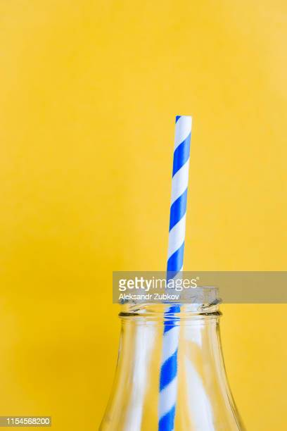 Colored, reusable, paper, striped, blue and white straws for drinking juice or cocktail life, in a glass bottle, on a yellow background. The concept of the festival, healthy eating, no plastic.