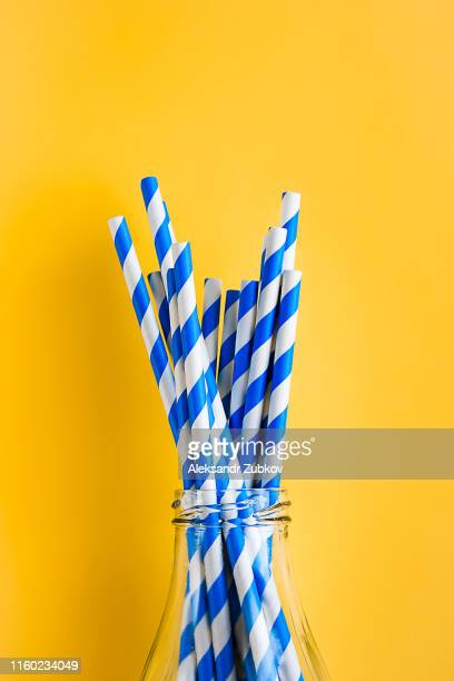 colored, reusable, paper, striped, blue and white straws for drinking juice or cocktail life, in a glass bottle, on a yellow background. the concept of the festival, healthy eating, no plastic. - drinking straw stock pictures, royalty-free photos & images