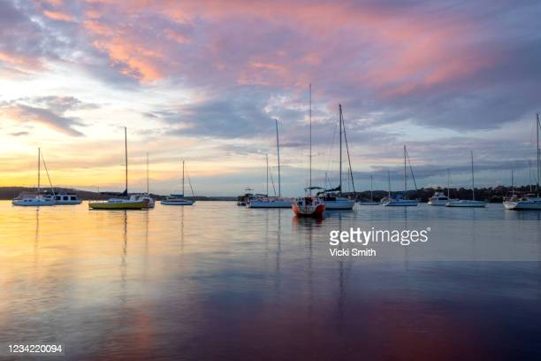 colored sunset over the water with boats and yachts - newcastle new south wales stock pictures, royalty-free photos & images