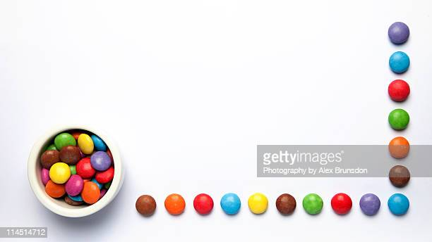 Colored sweets geometrically arranged white b/g