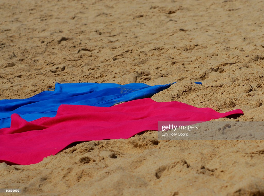 Colored towels on sandy beach : Stock Photo