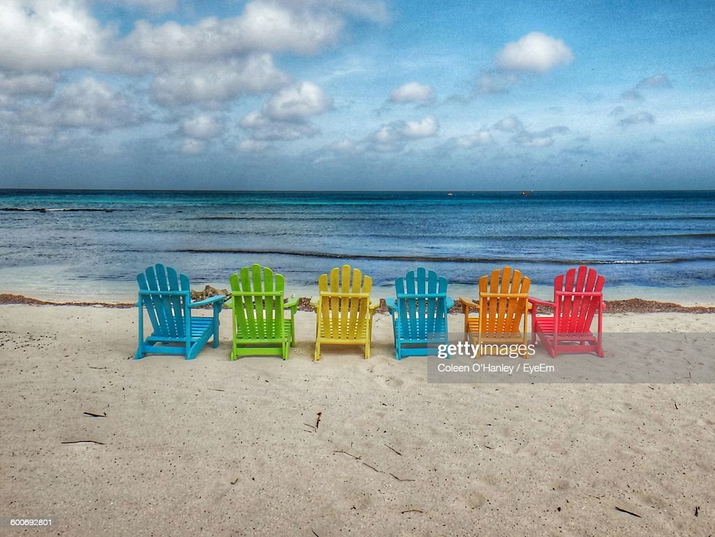 Colorful Adirondack Chairs On Sand At Beach Against Sky Stock