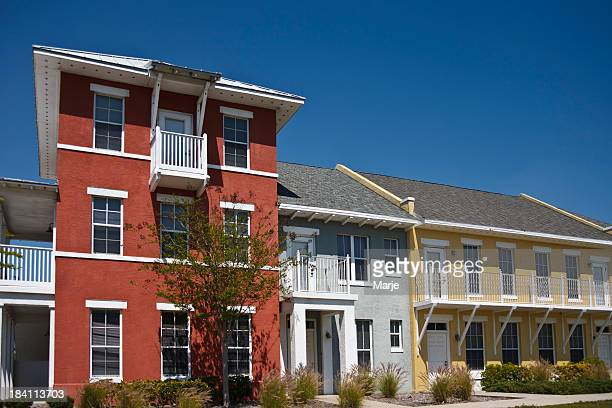 a colorful affordable housing complex under a clear sky - housing development stock pictures, royalty-free photos & images