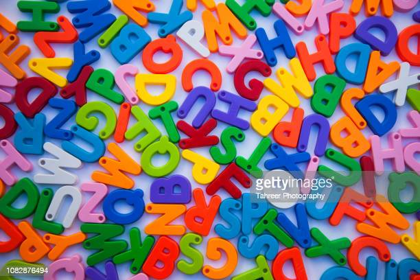 colorful alphabets blocks placed on white background - spelling stock pictures, royalty-free photos & images