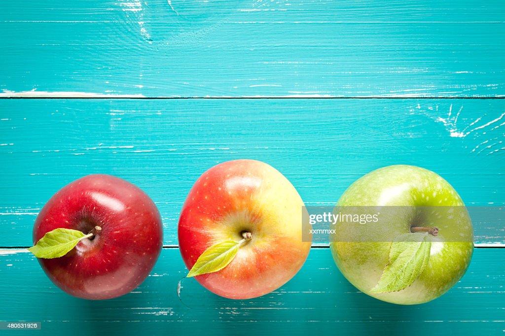 Bunte Äpfel auf Türkis Tisch : Stock-Foto