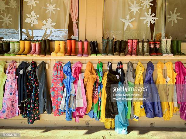 A colorful array of rain jackets and rain boots hung up in a row at a school