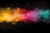 Colorful background of pastel powder explosion.Rainbow color dust splash on black background.