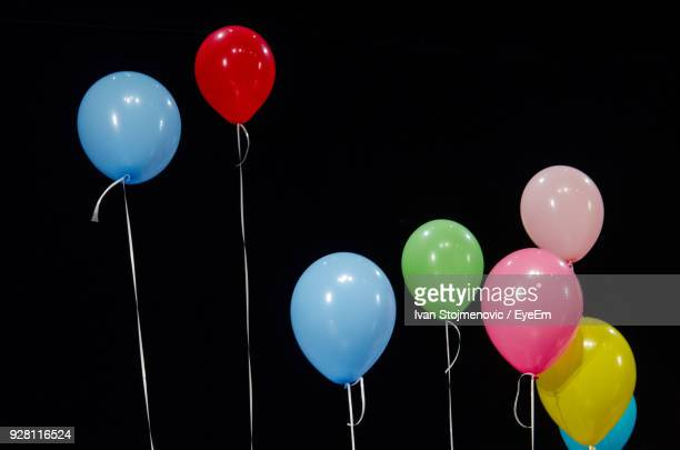 colorful balloons against black background - birthday balloons stock photos and pictures