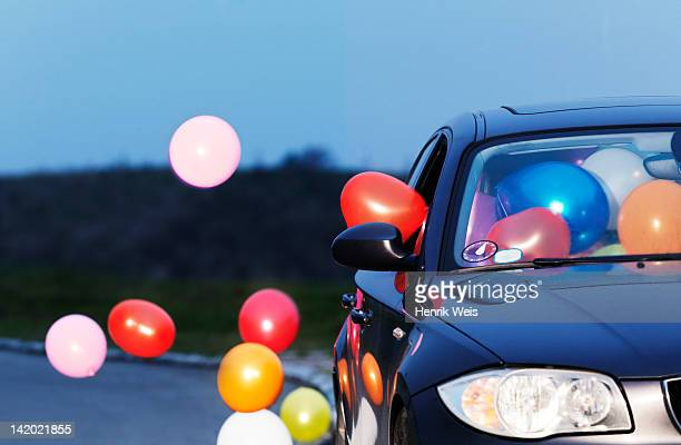 Colorful balloons coming out car window