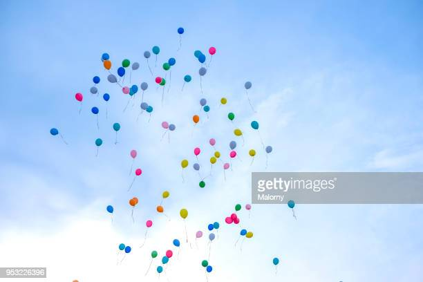 Colorful balloons flying away in blue sky. Wedding ceremony.