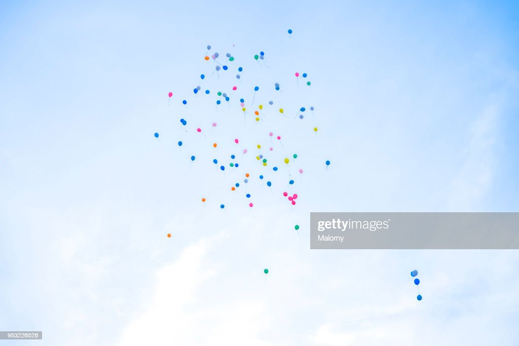 Colorful balloons flying away in blue sky. Wedding ceremony. : Stock Photo