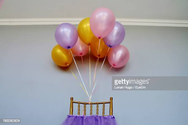 Colorful Balloons On Chair Against Wall