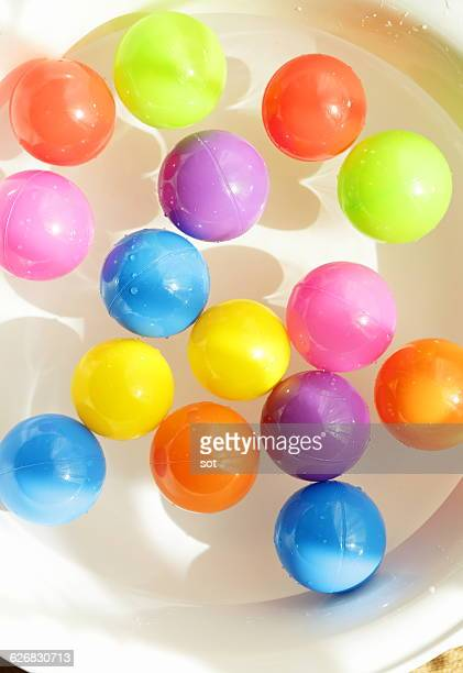 Colorful balls floating on water of washbowl