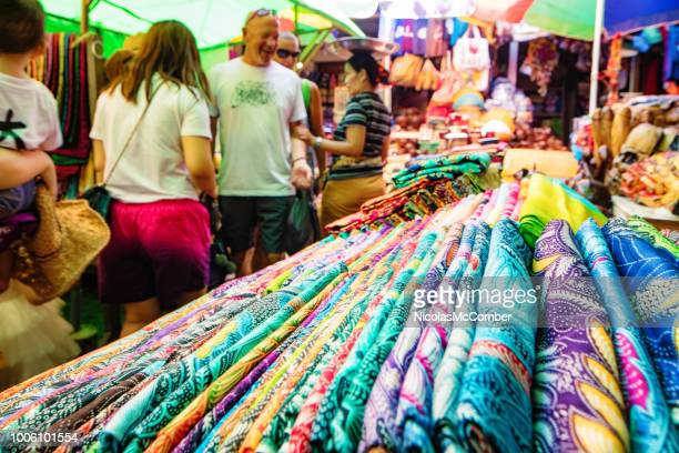 colorful batik fabric display with tourists visiting the ubud market in bali - batik stock pictures, royalty-free photos & images