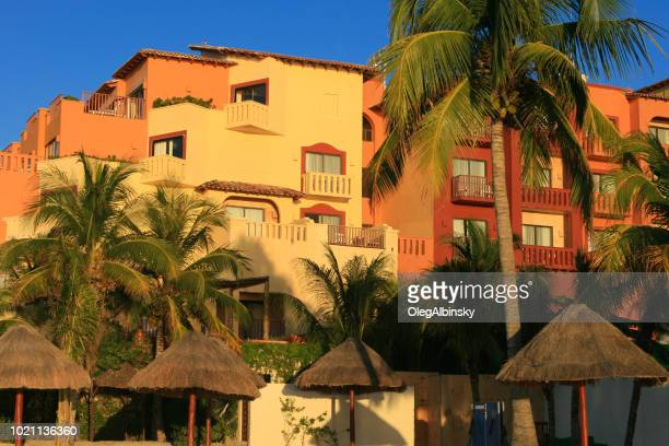 colorful beach resorts lit by the sunset sun at caribbean sea with blue sky, cancun, mexico. - quintana roo stock pictures, royalty-free photos & images