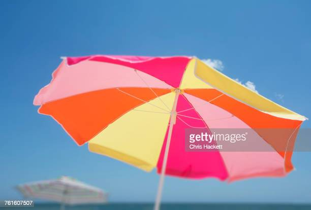 colorful beach umbrella against blue sky - sombrilla de playa fotografías e imágenes de stock