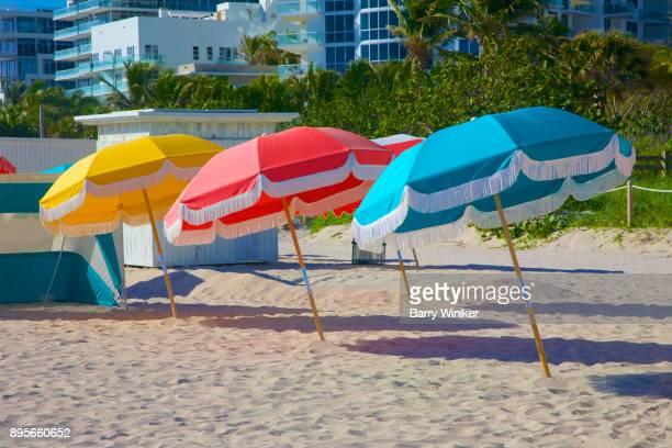 Colorful beach umbrellas tilted in sand, Miami Beach
