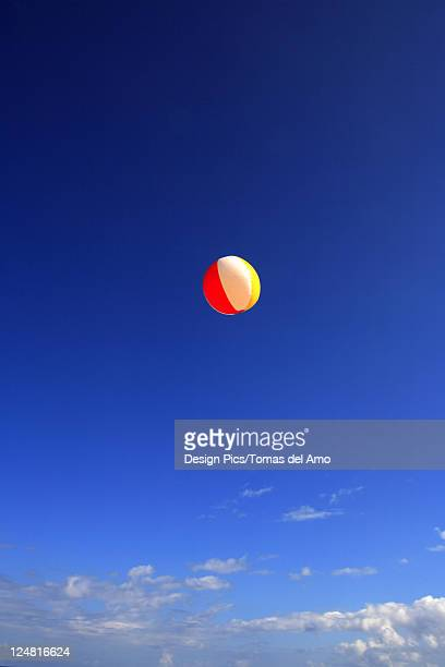 colorful beachball flying through bright blue sky. - blue balls pics stock pictures, royalty-free photos & images