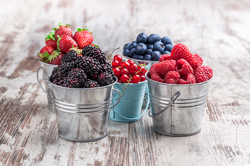 Colorful berries assortment in tin cans on rustic wooden table 856747054