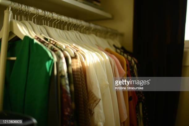 colorful blouses hanging in a row sorted by color - kristina strasunske stock pictures, royalty-free photos & images