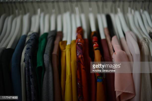colorful blouses hanging on a white hangers in a row - kristina strasunske stock pictures, royalty-free photos & images