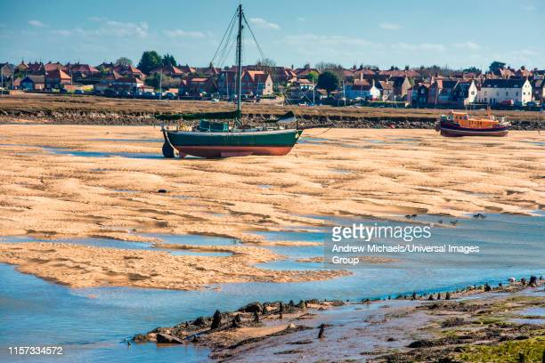 colorful boats marooned on sandbanks at low tide on east fleet river estuary at wells next the sea, north norfolk coast, east anglia, england, uk. - 英国ノーフォーク ストックフォトと画像
