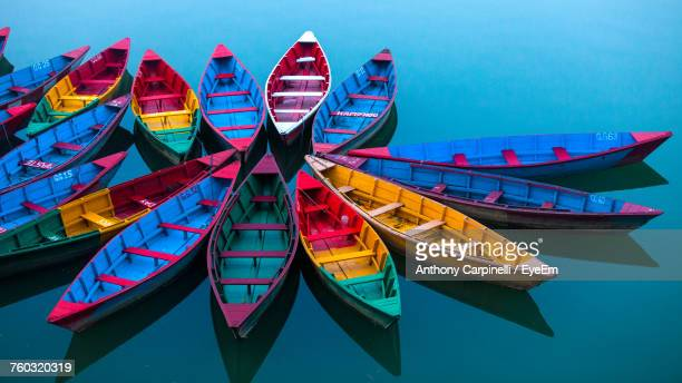colorful boats moored on lake - multi coloured stock pictures, royalty-free photos & images