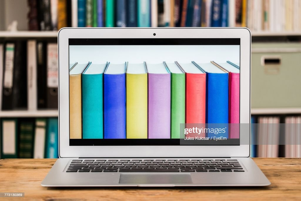Colorful Books On Laptop Screen At Table : Photo