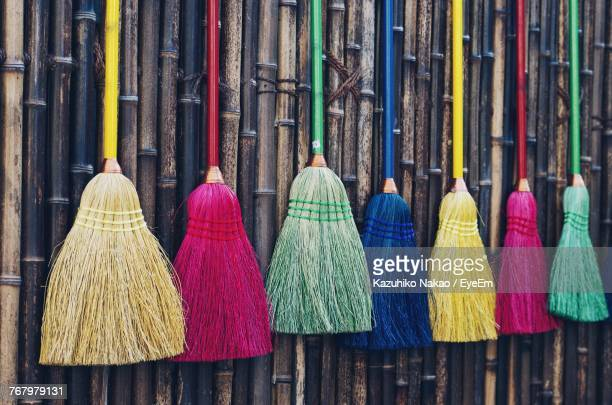 colorful brooms hanging for sale at market - broom stock pictures, royalty-free photos & images