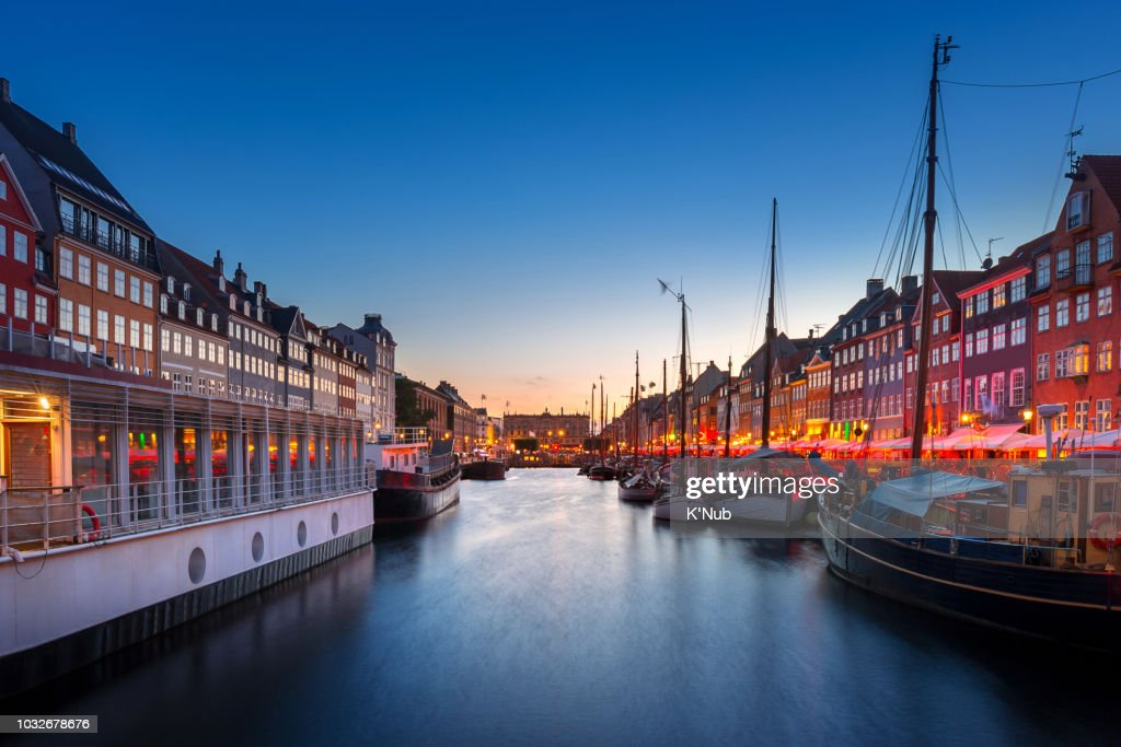 colorful building along the canal at Nyhavn, famous landmark for street food restaurant, with ship for transportation and tour around Copenhagen in Denmark, Europe, Scandinavia at sunset time : Stock Photo