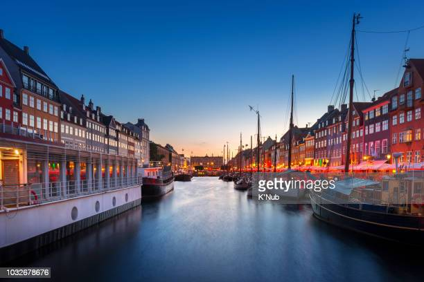 colorful building along the canal at nyhavn, famous landmark for street food restaurant, with ship for transportation and tour around copenhagen in denmark, europe, scandinavia at sunset time - nyhavn stock pictures, royalty-free photos & images