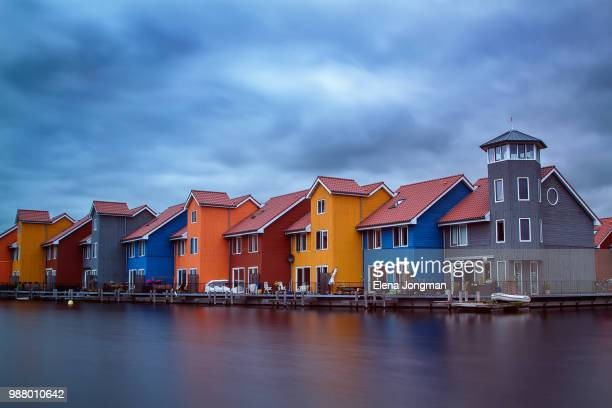 colorful buildings by sea, groningen, netherlands - groningen province stock photos and pictures