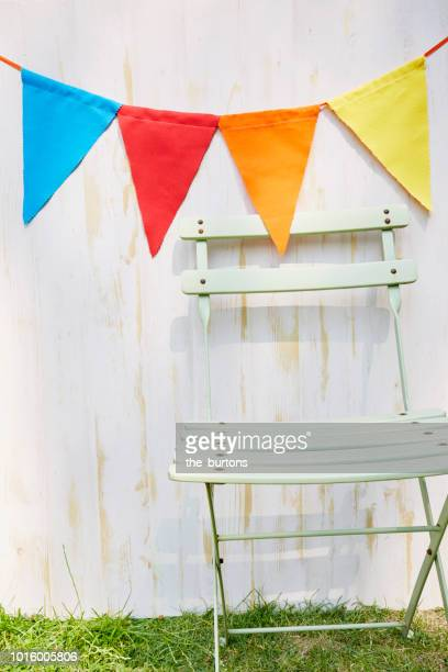 colorful bunting flags for party decoration at wooden wall in garden - garland decoration stock pictures, royalty-free photos & images