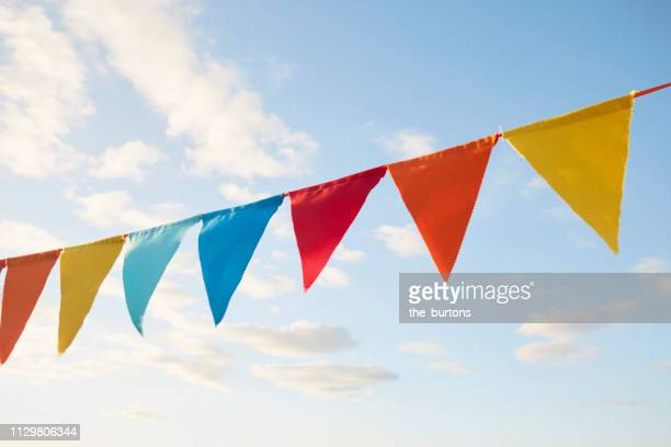 colorful bunting flags/ pennant chain for party decoration against sky - insígnia - fotografias e filmes do acervo