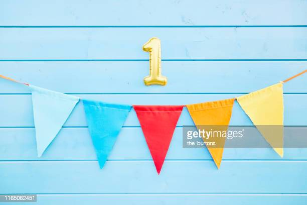 colorful bunting flags/ pennant chain for party decoration and gold colored number one at blue painted wooden wall - banderines fotografías e imágenes de stock