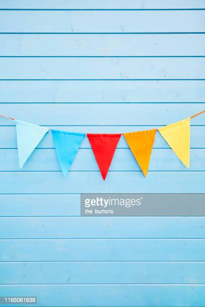 colorful bunting flags/ pennant chain for party decoration at blue painted wooden wall - bunting stock pictures, royalty-free photos & images