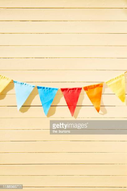 colorful bunting flags/ pennant chain for party decoration at yellow painted wooden wall in summer - bunting stock pictures, royalty-free photos & images