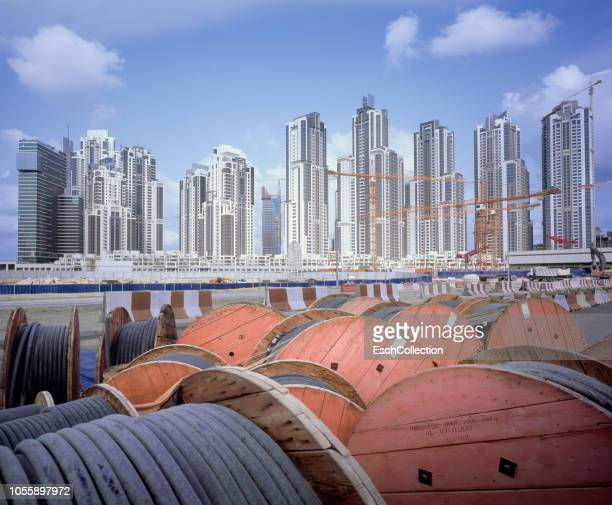 Colorful cable drums in front of large construction site in Dubai