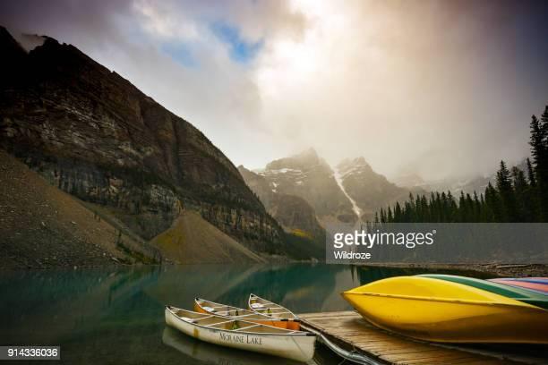 colorido canoas en el lago de morrena - alberta fotografías e imágenes de stock