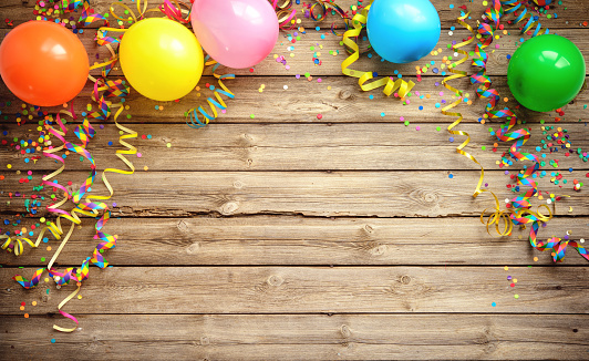 Colorful carnival or party frame of balloons, streamers and confetti on rustic wooden board 911842696