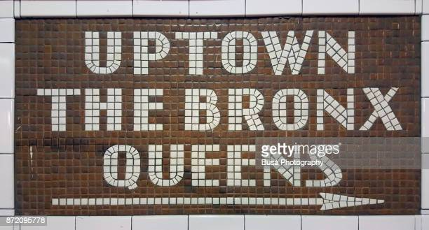 New York City, NY, USA - October 10, 2017: Colorful ceramic plaques and tile mosaics in the New York City subway. Mosaic directing passengers in direction: Uptown - The Bronx - Queens