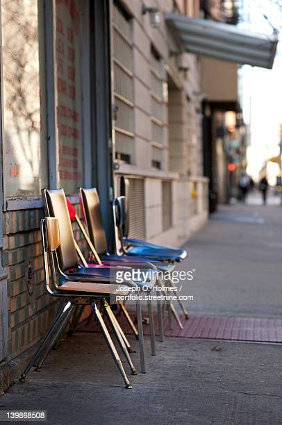 colorful chairs line up on street - joseph o. holmes stock pictures, royalty-free photos & images