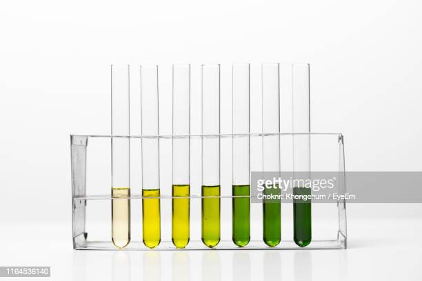 colorful chemicals in laboratory glassware against white background - vial stock pictures, royalty-free photos & images