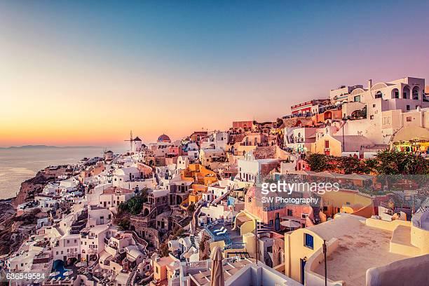 colorful city and golden sunset - oia santorini foto e immagini stock