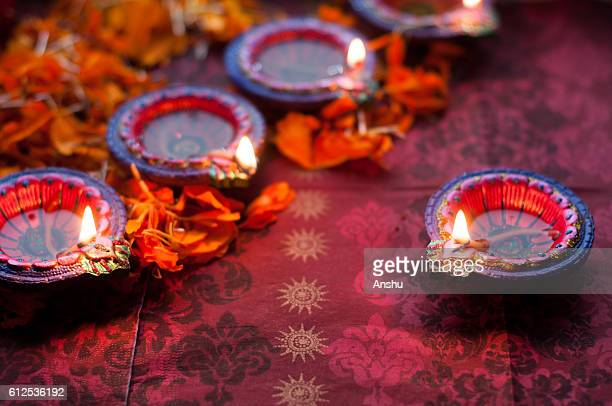Colorful clay diya lamps lit during diwali celebration with flowers