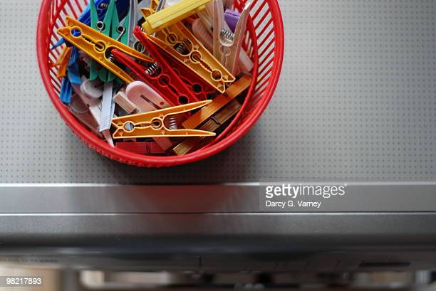 Colorful clothespins in red basket on washer