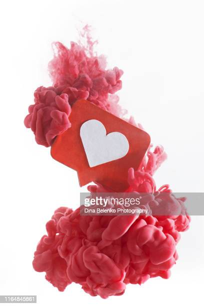 colorful cloud around a red like icon with a heart. dissolving in social media concept. red paint on a white background with copy space - like button stock pictures, royalty-free photos & images