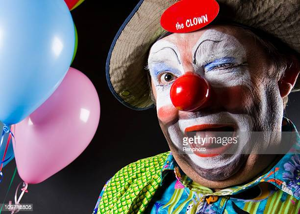 bunte clown zwinkern in die kamera - clown stock-fotos und bilder