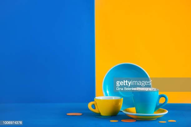 Colorful coffee cups on a vibrant blue and yellow background. Color block coffee in food photography. Suprematic concept with copy space. Modern coffee brewing