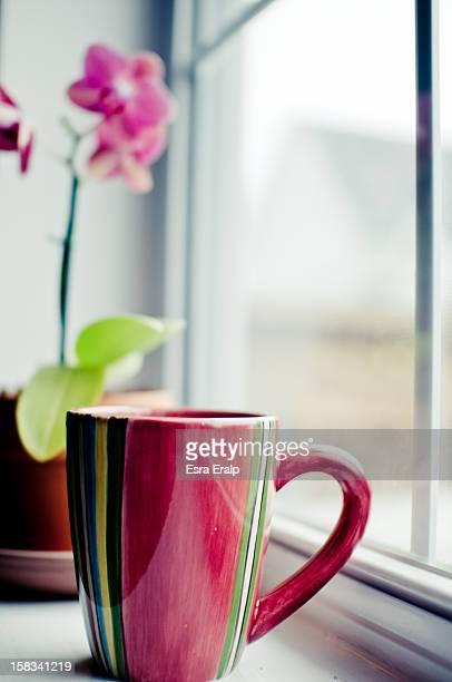 Colorful coffee mug in the windowsill